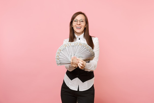 Young smiling successful business woman in glasses holding bundle lots of dollars, cash money isolated on pink background. lady boss. achievement career wealth concept. copy space for advertisement.