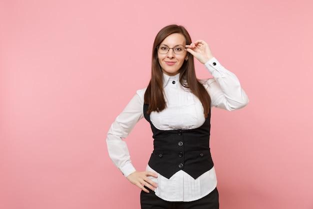 파스텔 핑크색 배경에 격리된 안경을 들고 검은 양복과 흰색 셔츠를 입은 젊은 웃고 있는 성공적인 비즈니스 여성. 여사장님. 성취 경력 부 개념입니다. 광고 공간을 복사합니다.