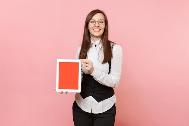 파스텔 핑크색 배경에 격리된 빈 화면이 있는 태블릿 pc 컴퓨터를 들고 정장 안경을 쓰고 웃고 있는 성공적인 비즈니스 여성. 여사장님. 성취 경력 부 개념입니다. 공간을 복사합니다.