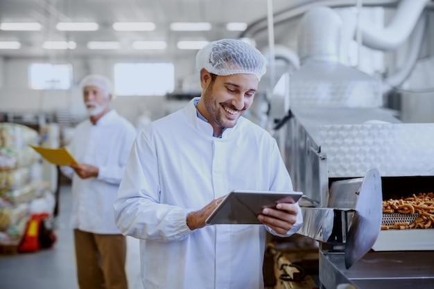 Молодой улыбающийся руководитель в стерильной белой форме с помощью планшета и проверки качества соленых палочек. на заднем плане старый руководитель держит папку с документами. интерьер пищевого завода.