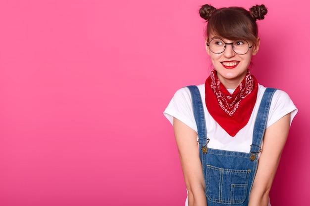 Молодая улыбающаяся милая девушка смотрит в сторону, одетая в повседневную белую футболку, джинсовый комбинезон, красную бандану и круглые модные очки, находясь в приподнятом настроении, имея гроздья. скопируйте место для рекламы.