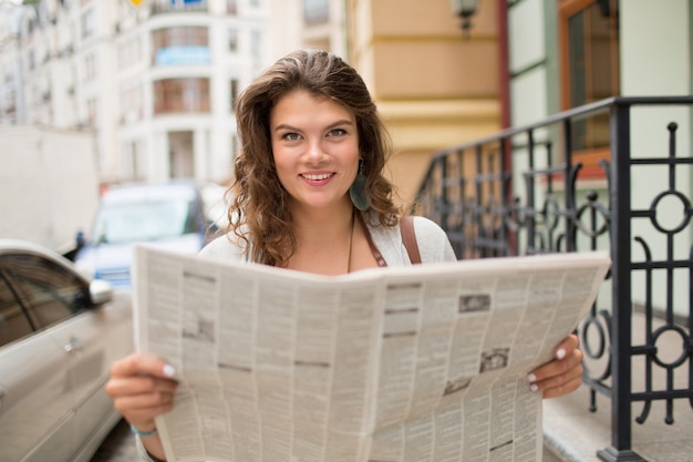 Young smiling tavel girl holding newspaper.
