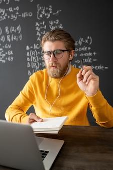 온라인 수업의 시작 부분에 그를 인사하는 동안 이어폰이 온라인 학생 중 한 명에게 손을 흔들며 젊은 웃는 교사
