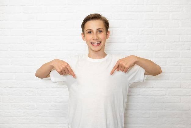若い笑顔の十代の少年はあなたのtシャツの空きスペースに彼の指を示しています。コピースペース