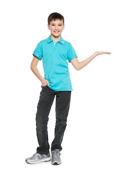 Il giovane ragazzo teenager sorridente mostra qualcosa sul palmo isolato su bianco.