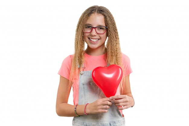 Young smiling teen girl congratulating on holiday with red heart balloon on isolated white .
