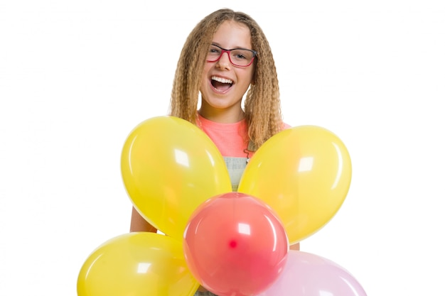 Young smiling teen girl with festive color balloons on isolated white .
