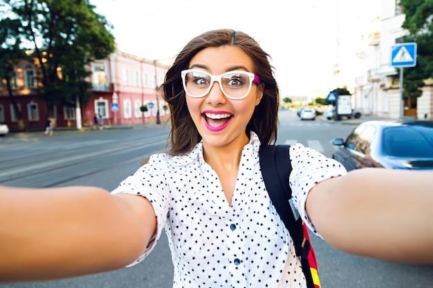 재미, 긍정적 인 분위기, 기쁨, 휴가, 혼자 여행, 거리에서 셀카를 만드는 젊은 웃는 사춘기 행복한 여자, 링 머리카락, 밝은 메이크업과 귀여운 맑은 안경,