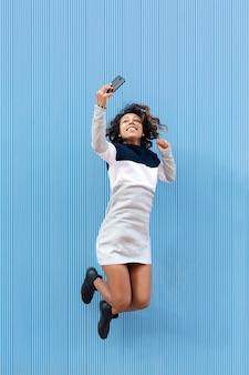 若い、笑顔の10代の少女が上下にジャンプし、彼女の携帯電話で写真を撮る