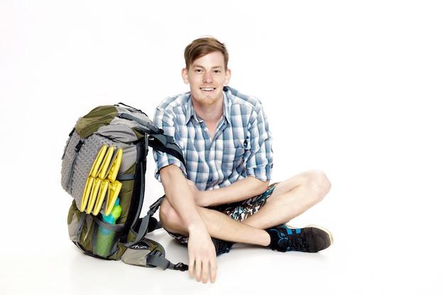 Молодой улыбающийся турист сидит с рюкзаком на белом фоне. путешественник готовится к походу