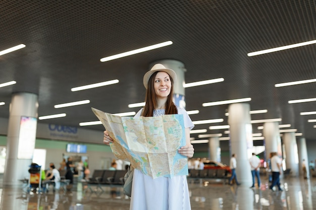 Young smiling traveler tourist woman in hat holding paper map, looking aside while waiting in lobby hall at international airport