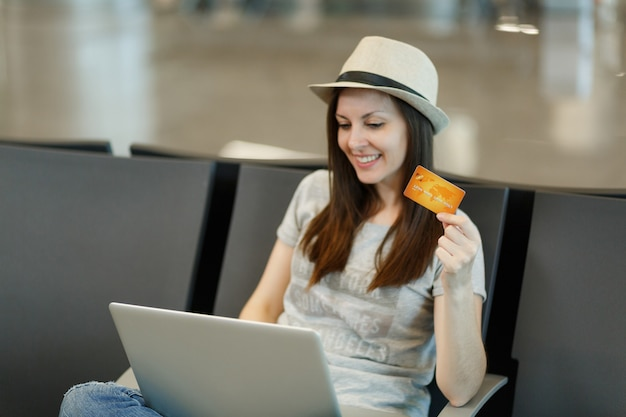 Young smiling traveler tourist woman in hat sitting and working on laptop, holding credit card, waiting in lobby hall at airport