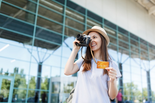 Young smiling traveler tourist woman in hat, take pictures on retro vintage photo camera, hold credit card at international airport