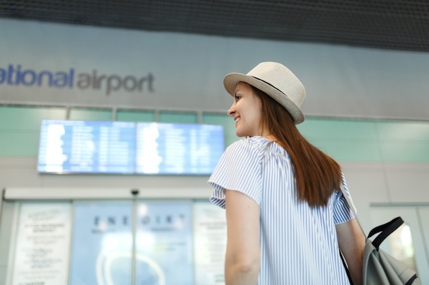 Young smiling traveler tourist woman in hat with backpack look on schedule, timetable, wait in lobby hall at international airport