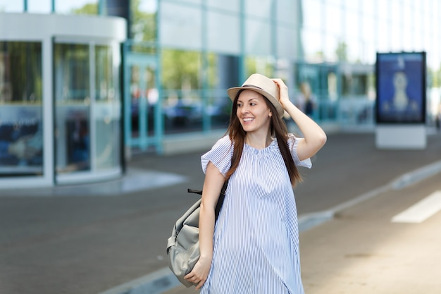 Young smiling traveler tourist woman in hat with backpack standing at international airport
