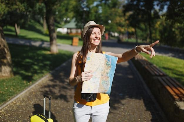 도시 야외에서 검지 손가락을 가리키는 여행 가방 도시 지도와 캐주얼 옷 모자에 젊은 웃는 여행자 관광 여성. 주말 휴가를 여행하기 위해 해외로 여행하는 소녀. 관광 여행 라이프 스타일.