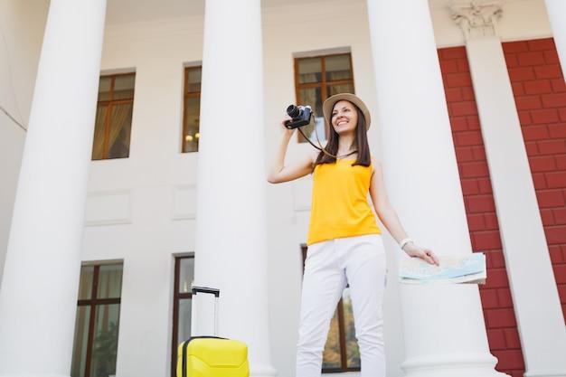 Молодая улыбающаяся туристическая женщина путешественника в повседневной одежде с картой города чемодана фотографирует на открытом воздухе ретро винтаж фотоаппаратом. девушка выезжает за границу на выходные. туризм путешествие образ жизни.