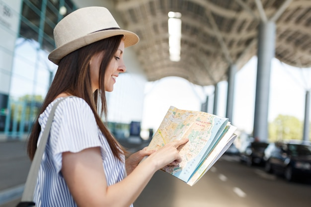 国際空港で紙の地図でルートを検索するバックパックと帽子をかぶった若い笑顔の旅行者観光客の女性