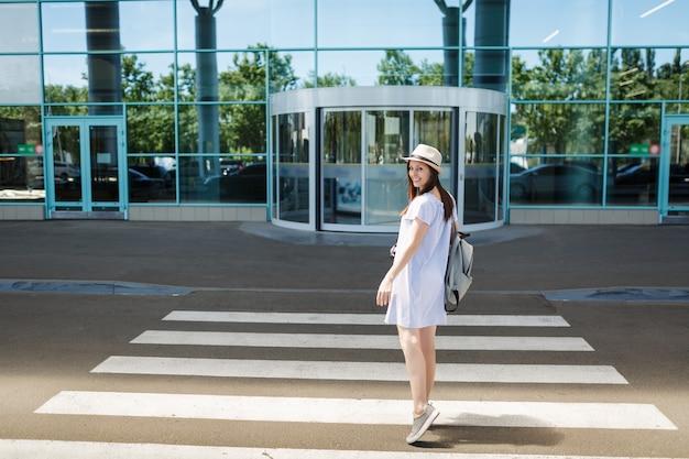 国際空港の横断歩道で振り返るバックパックと帽子をかぶった若い笑顔の旅行者観光客の女性