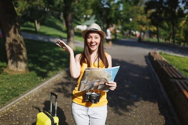 노란 옷을 입고 웃고 있는 젊은 여행자 관광 여성, 여행가방을 든 모자는 도시 야외에서 도시 지도를 들고 손을 펼쳤습니다. 주말 휴가를 여행하기 위해 해외로 여행하는 소녀. 관광 여행 라이프 스타일.