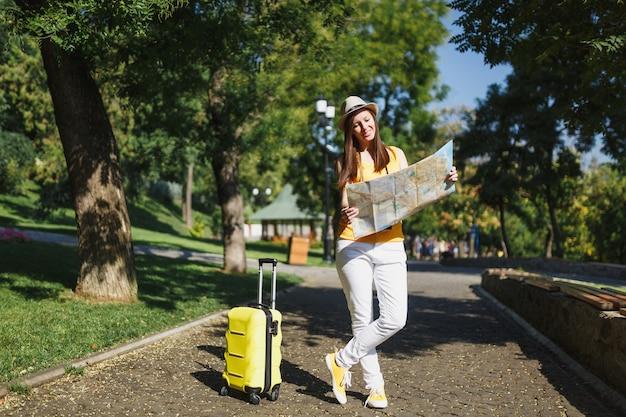 노란색 여름 캐주얼 옷을 입은 젊은 여행자 관광 여성, 여행 가방 도시 지도가 있는 모자가 도시 야외에서 산책합니다. 주말 휴가를 여행하기 위해 해외로 여행하는 소녀. 관광 여행 라이프 스타일.