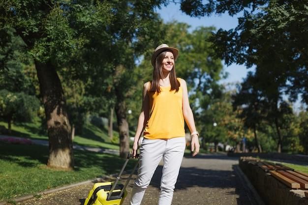 Молодая улыбающаяся туристическая женщина путешественника в желтой летней повседневной одежде, шляпе с чемоданом, идущей в городском парке на открытом воздухе. девушка едет за границу, чтобы поехать на выходные. туризм путешествие образ жизни.