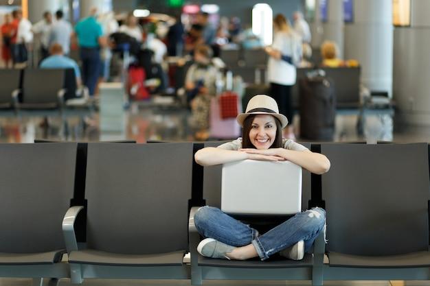 国際空港のロビーホールで待っている間、足を組んでノートパソコンで座っている若い笑顔の旅行者観光客の女性