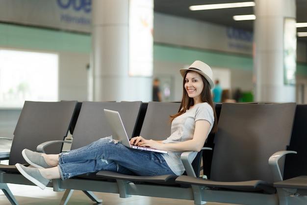 Giovane turista turista sorridente seduta che lavora al computer portatile mentre aspetta nella hall dell'aeroporto internazionale