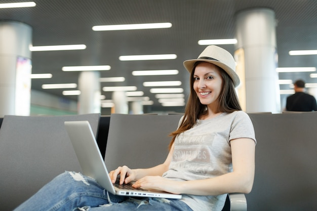国際空港のロビーホールで待っている間ラップトップに取り組んで座っている若い笑顔の旅行者観光客の女性