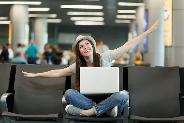 La giovane donna turistica sorridente del viaggiatore con il computer portatile si siede con le gambe incrociate che allargano le mani come in volo che aspetta nella hall dell'aeroporto