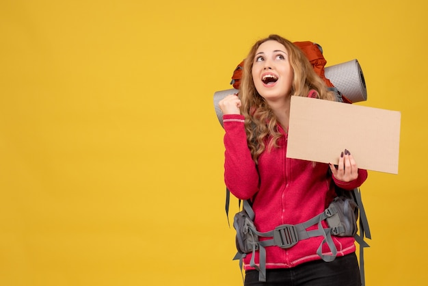 Young smiling travelling girl collecting her luggage showing free space for writing and looking up