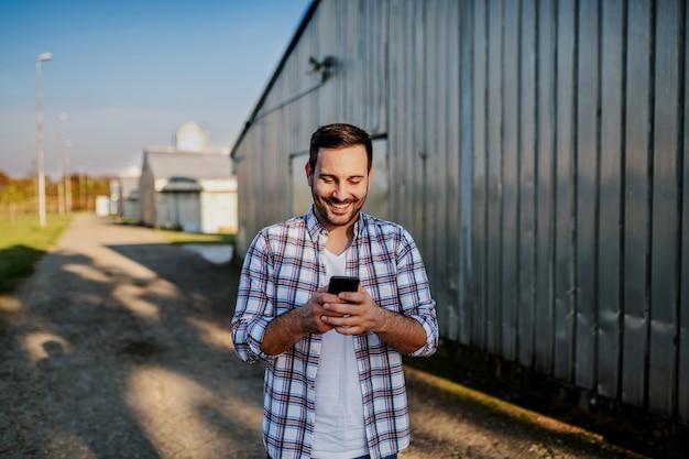 Молодой улыбающийся небритый кавказский фермер, стоящий рядом с сараем и использующий смартфон для текстовых сообщений.