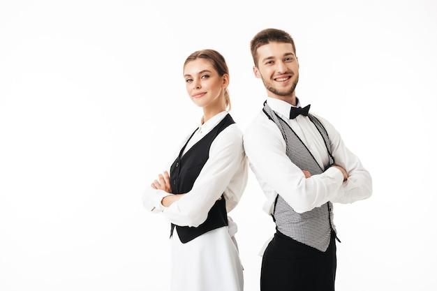若い笑顔のウェイターと白いシャツとベストの美しいウェイトレスが幸せに背中合わせに立っています