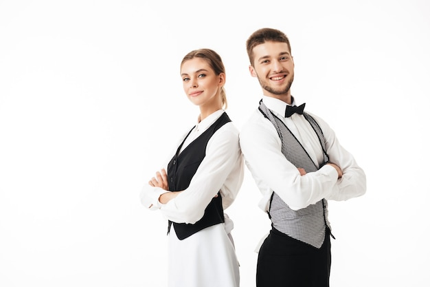 Young smiling waiter and beautiful waitress in white shirts and vests sstanding back to back while happily