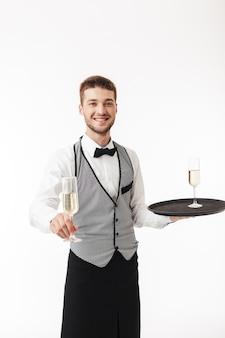 カメラにシャンパングラスを提供しながら、喜んでトレイを保持している制服を着た若い笑顔のウェイター
