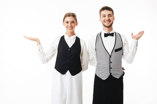 Young smiling waiter and pretty waitress in white shirts and vests happily