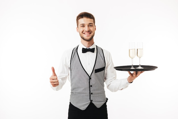 Young smiling waiter in uniform happily