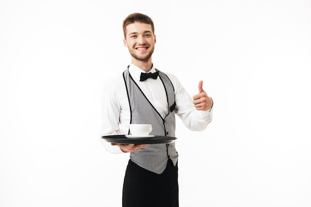 Young smiling waiter in uniform holding tray with cup of coffee in hand joyfully