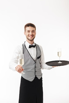 Young smiling waiter in uniform joyfully holding tray while offering glass of champagne on camera