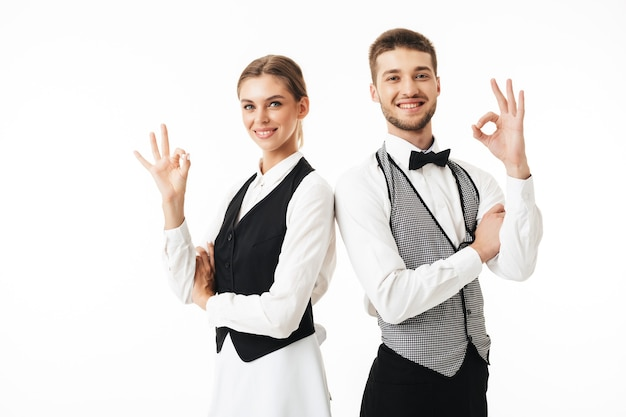Young smiling waiter and waitress in white shirts and vests sstanding back to back happily