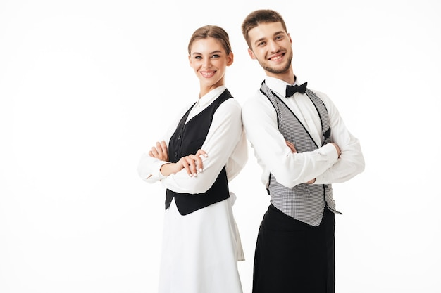 Young smiling waiter and waitress in white shirts and vests sstanding back to back while joyfully