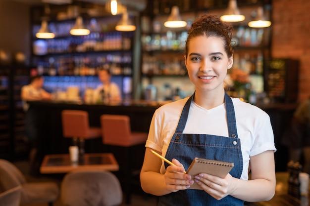 豪華なレストランでカメラの前に立って、クライアントの注文を書き留める作業服の若い笑顔のウェイトレス