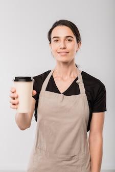 孤立してカメラの前に立っている間あなたにホットコーヒーの紙ガラスを与えるカフェの若い笑顔のウェイトレス
