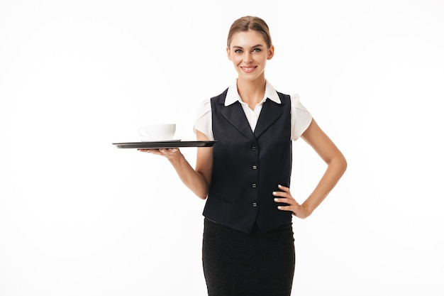 Young smiling waitress in uniform holding tray with cup of coffee while dreamily