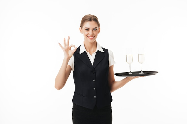 Young smiling waitress in uniform holding tray with glasses happily