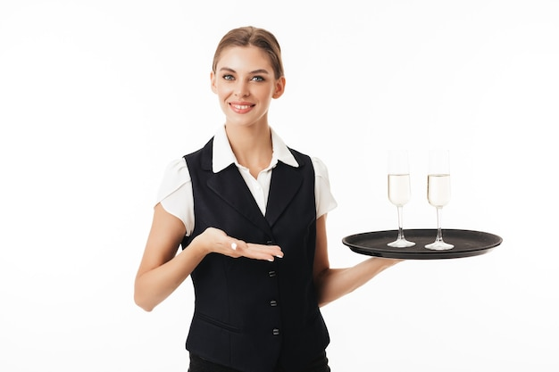 Young smiling waitress in uniform holding tray with glasses joyfully