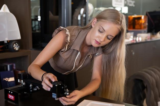 실험실에서 과학 실험을 하는 동안 기계 부품을 분석하는 젊은 웃는 여성.