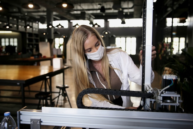 Young smiling woman analyzing machine part during her scientific experiment in laboratory.