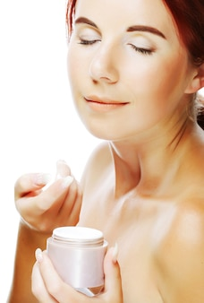 Young smiling woman applying cream on her face