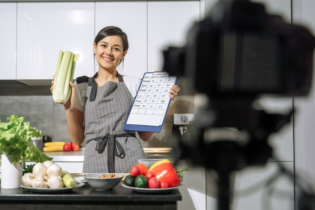 Young smiling woman in an apron holding celery and a comparative table of calorie content of products in her hands and recording video on a camera in the kitchen